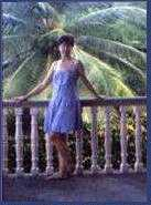 [A woman standing on the second  floor of a veranda with a palm tree spreading its leaves behind her.]